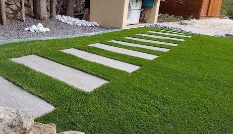 chemin pavé sur une pelouse synthétique