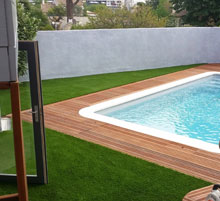 piscine entourée de bois et de pelouse
