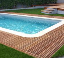 piscine avec bois et pelouse artificielle